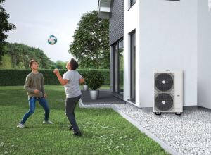 Two boy in garden playing football near house with air source heat pumps